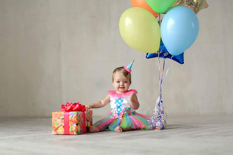 baby girl celebrating first birthday with gift