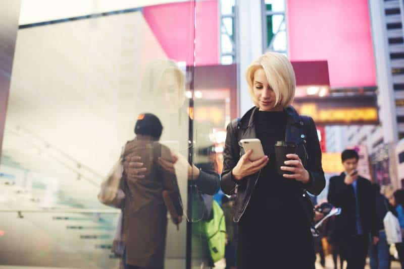Attractive female traveller dressed in stylish casual wear holding smartphone and walking in the street