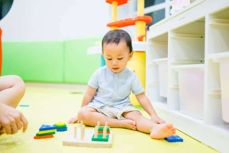 2.5 years old baby boy playing with lots of wooden toys block with mother