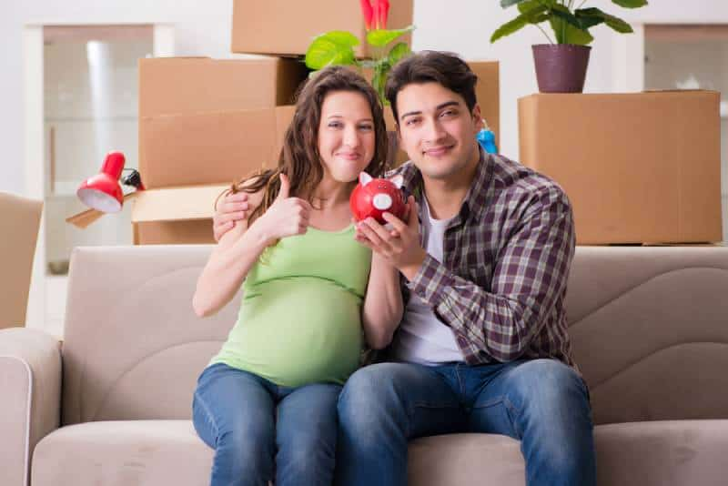 Young couple in new house saving money for baby to be born