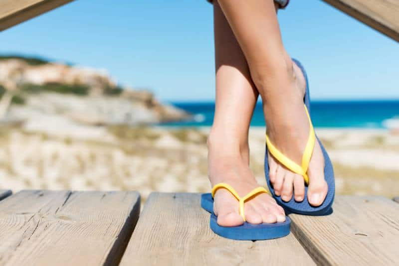 Low section of woman wearing yellow blue slippers while standing on board walk
