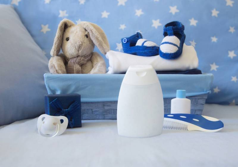 baby background with blue basket, plush toy, bootees, pacifier, toiletries and gift box