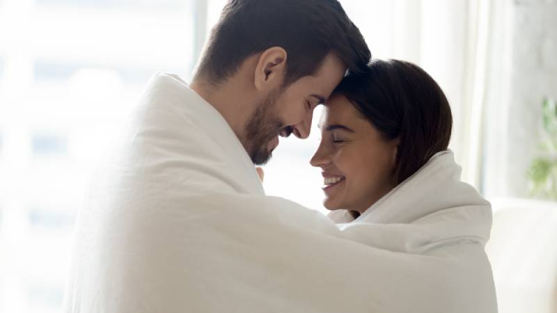 Side view head shot close up young bonding family couple covered in warm cozy blanket touching foreheads