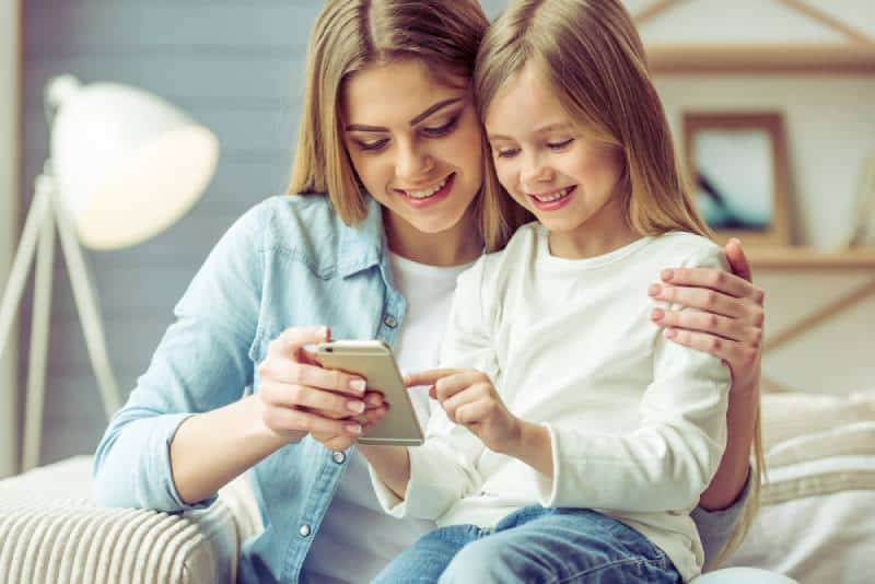 young mom and her little daughter are using a smartphone and smiling while sitting on sofa at home
