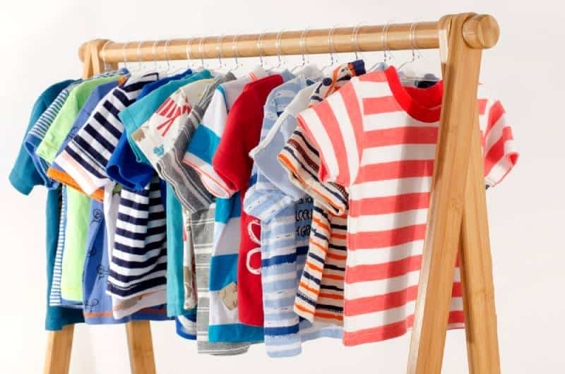 Dressing closet with colorful wardrobe of newborn kids, toddlers, babies full of all clothes