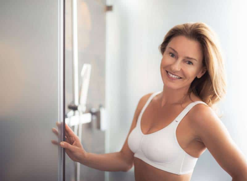 portrait of charming lady in white bra holding door and smiling