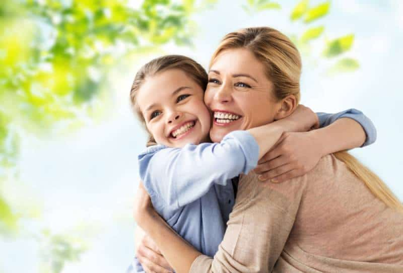 happy smiling mother hugging daughter over green natural background