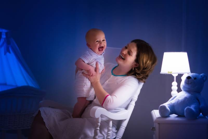 Mother and baby reading a book and having fun before bedtime in dark bedroom