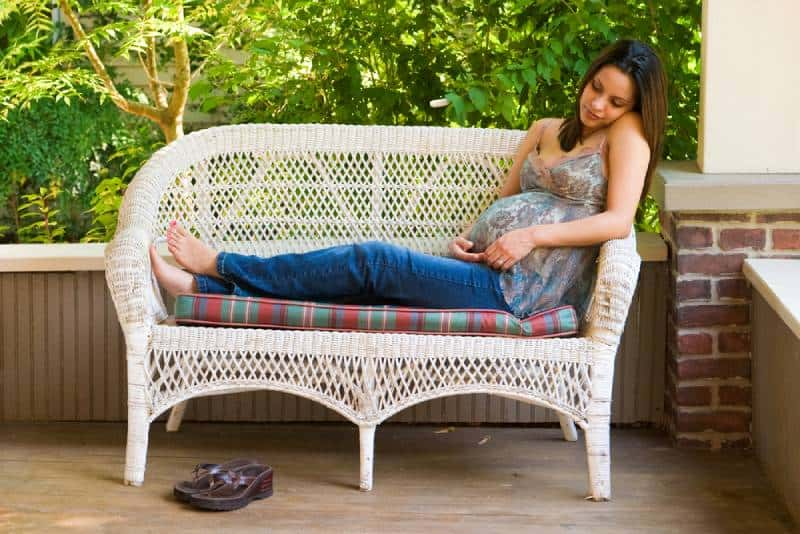 A beautiful young pregnant woman in jeans and colorful blouse relaxing outside white waiting for the birth of her baby