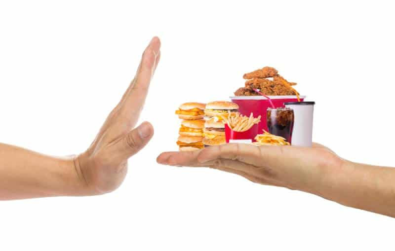 Hand refusing junk food with white background