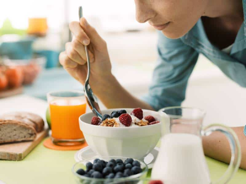 Woman having an healthy delicious breakfast at home, she is eating yogurt with cereals and fresh fruit, healthy food concept
