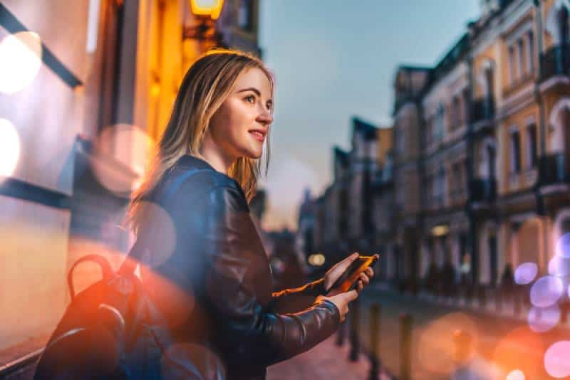 blonde female tourist with a backpack walking through night city street with mobile phone in hands