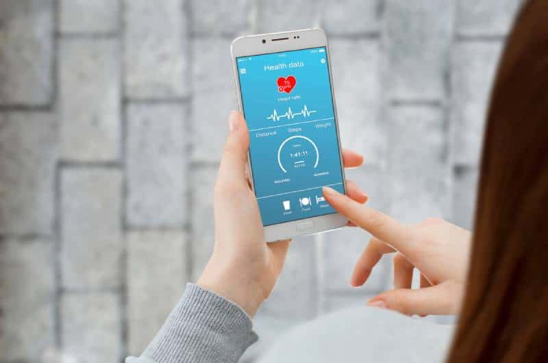 Girl using smartphone app to check her health data while walking on the street
