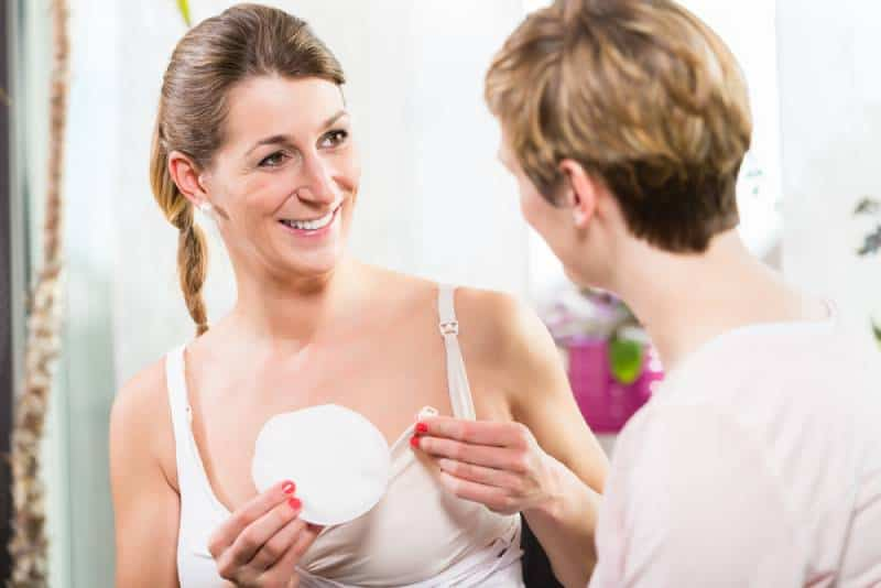 Woman in white using comfortable plastic breast shells inside bra for collecting excess breast milk
