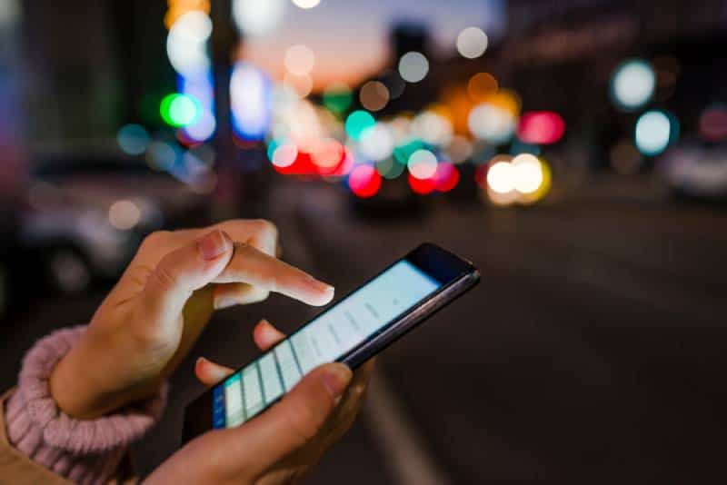 Close-up of woman's hand using phone in night time on street