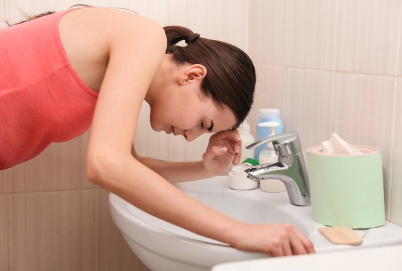Young vomiting woman in red shirt near sink in bathroom