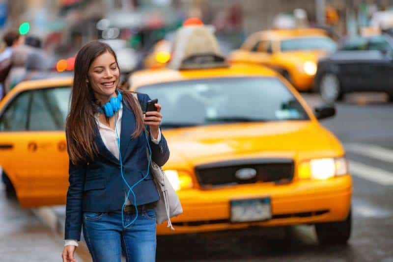 Young woman in jeans walking in New York city using phone app
