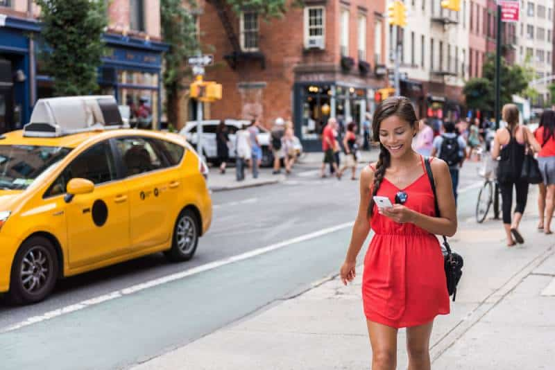 Woman in red dress walking in new york city and using her phone