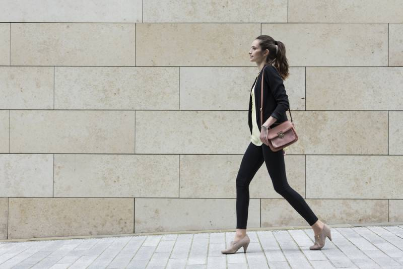 Businesswoman walking on city street in front of modern marble wall