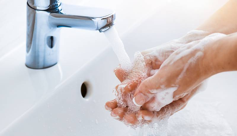 Woman use soap and washing hands under the water tap