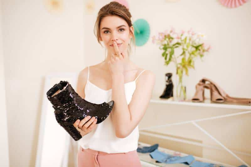 Pretty lady wearing white top standing in clothes store with black boot in hands and thoughtfully looking in camera