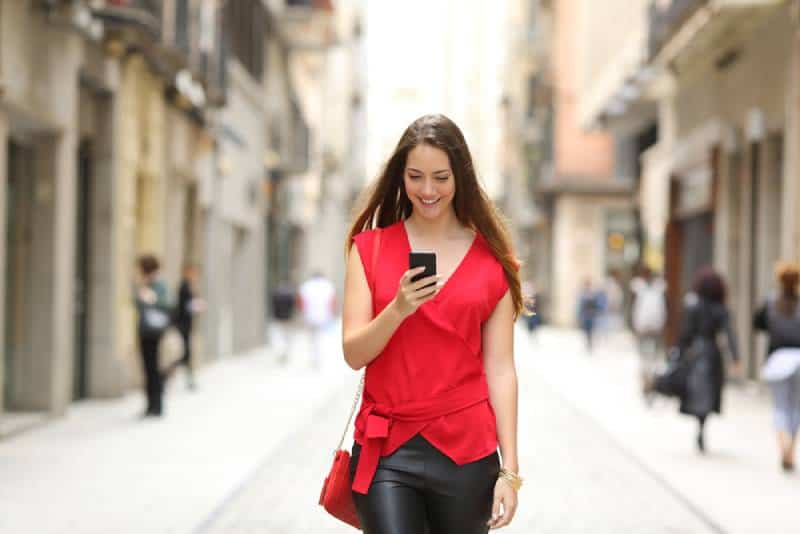 Front view of a fashion happy woman in red shirt and black pants walking and using a smart phone on a city street