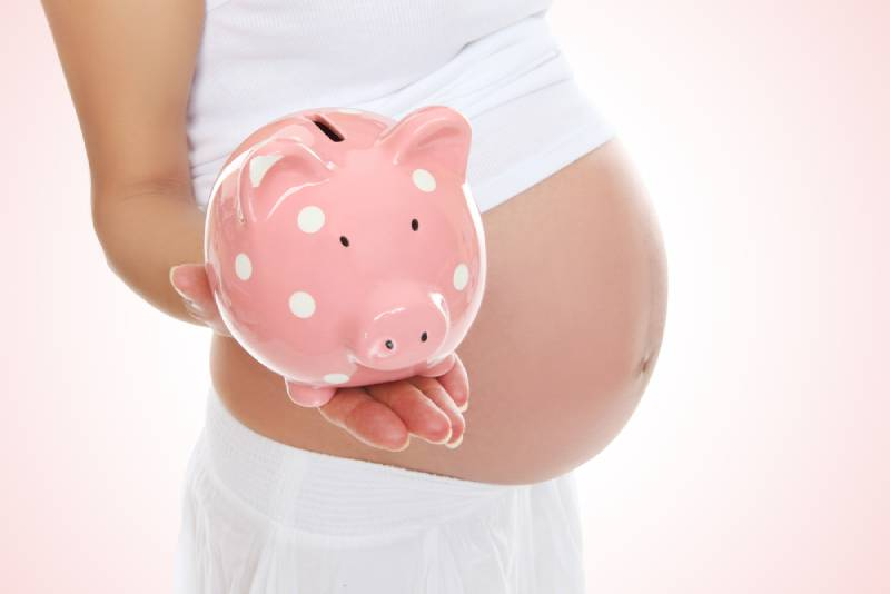 A pregnant mom in white to be holding a piggy bank