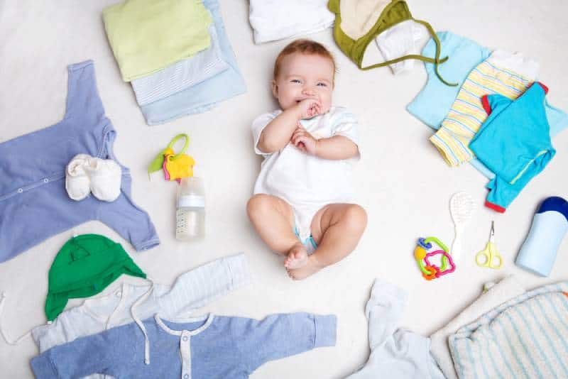 Smiling baby on white background with clothing, toiletries, toys and health care accessories