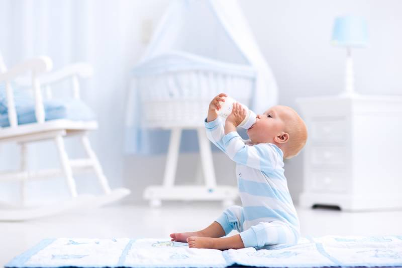 baby boy playing on a blue floor mat and drinking milk from a bottle in a white sunny nursery with rocking chair and bassinet