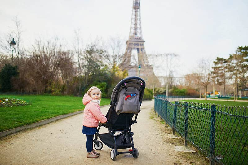 baby girl in France with stroller in front of the Eiffel Tower
