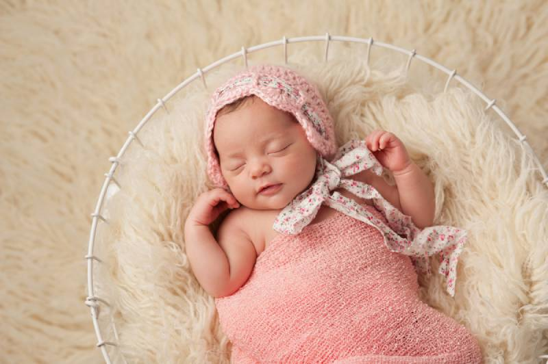 A portrait of a five week old newborn baby girl wearing a pink bonnet and lying in a basket