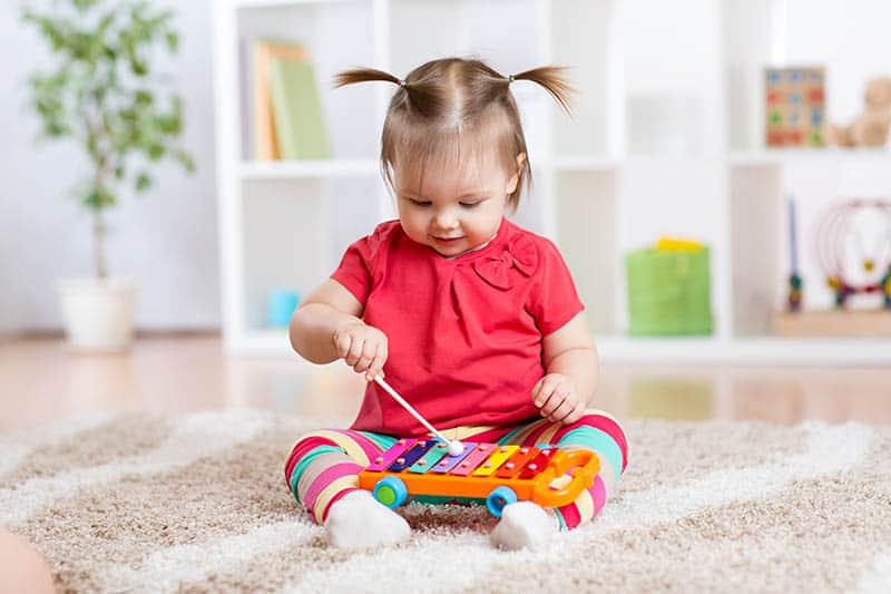 cute baby girl playing with musical instrument