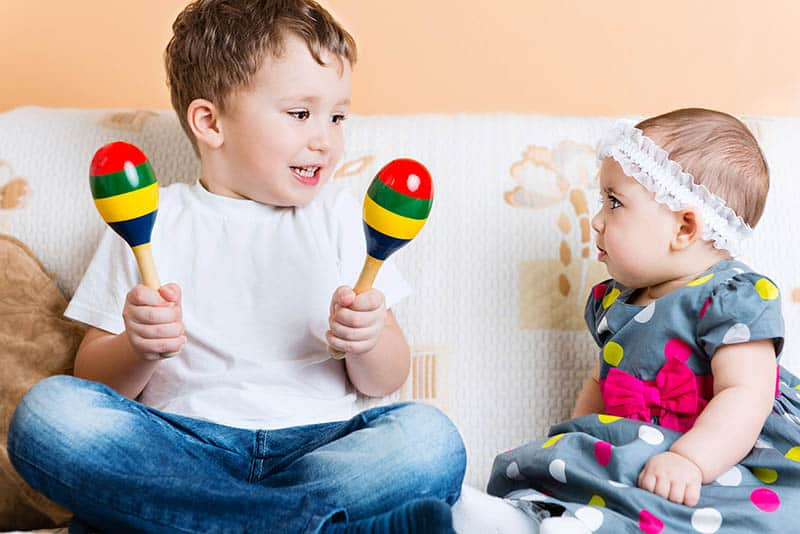 baby toddler siblings playing with musical instruments