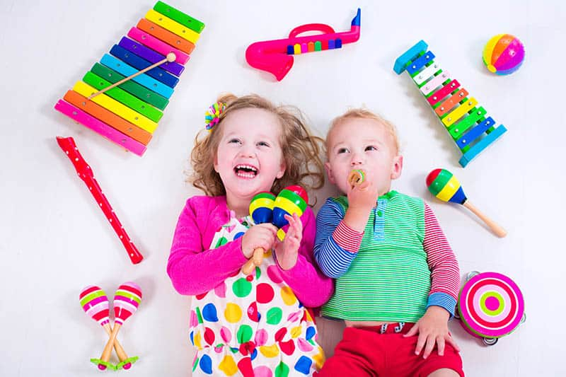 two toddlers playing with musical instruments