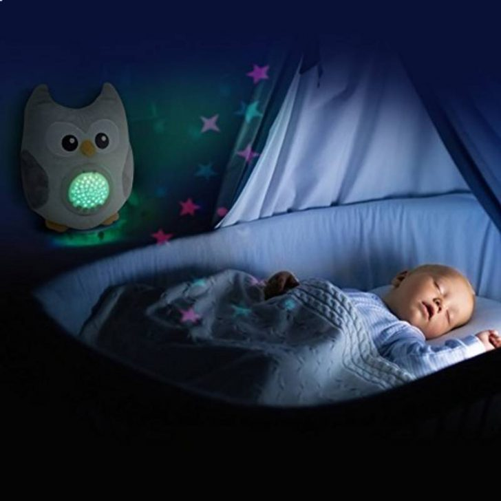 baby sleeping in a crib next to the baby projector