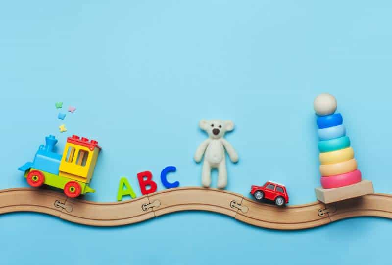 Kids toys train, ABC letters, bear, car and pyramid on toy wooden railway on blue background