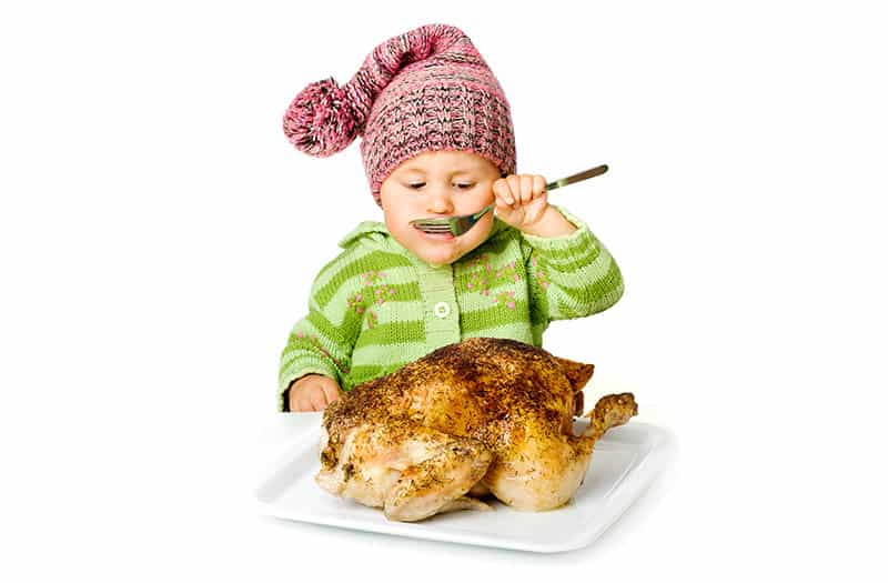 isolated baby with big baked chicken pretending to eat with spoon