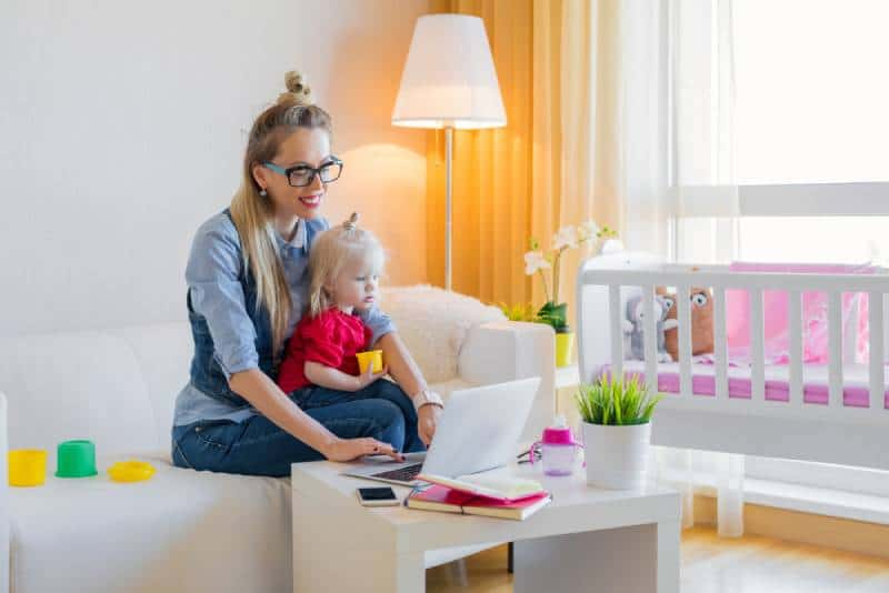 Stay at home mom working on laptop with kid on her lap in her living room