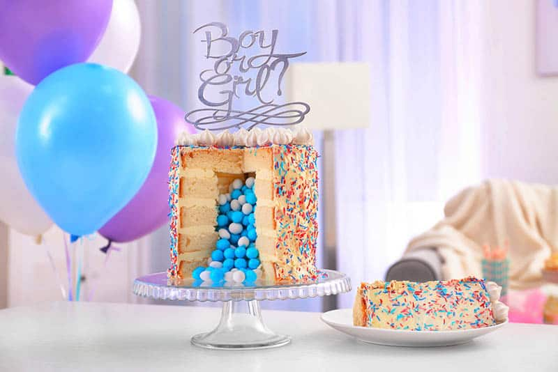 Gender reveal games with cake and balloons on the table