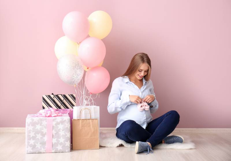 Beautiful pregnant woman with baby shower gifts near pink wall