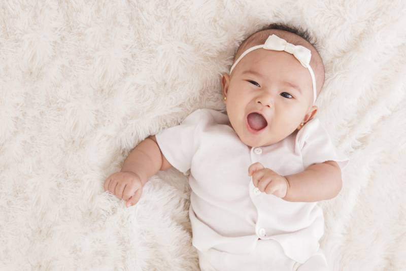 smiling baby girl in cute clothes lying in crib