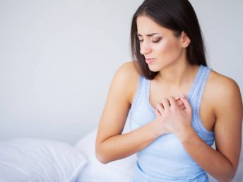 Beautiful lady with breast pain sitting on the bed with sad expression on her face