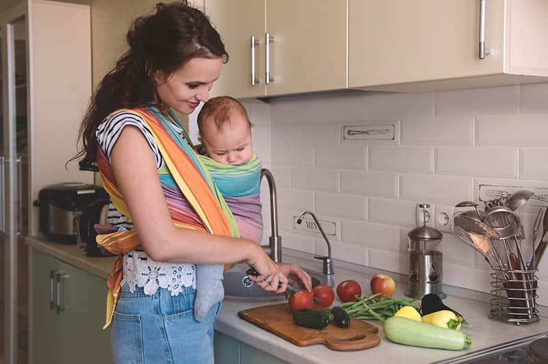 woman with baby making dinner