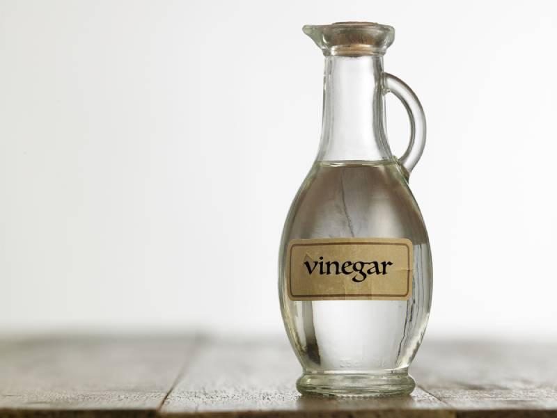 Bottle of white vinegar on the wooden table top