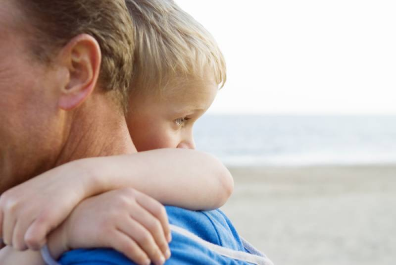 Child hugs father and looking in the distance while being at the beach