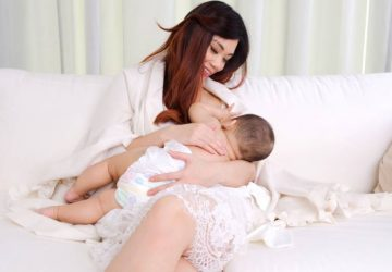 Mom in white clothes breastfeeding her baby on sofa in a room