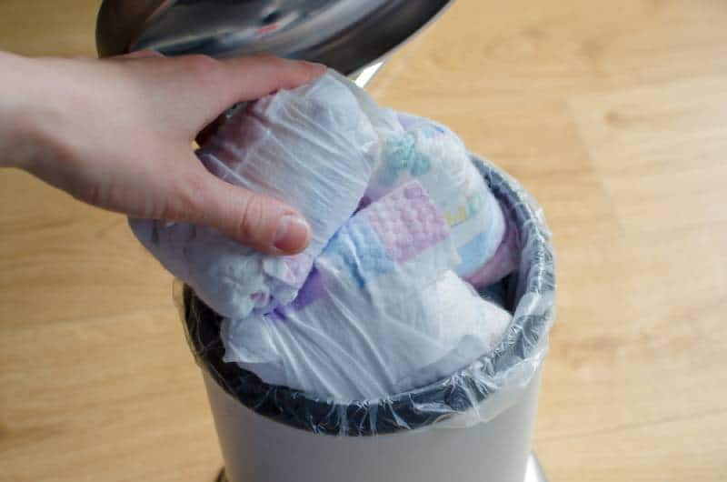 Woman hand put used diaper to the Trash bin full of used diapers