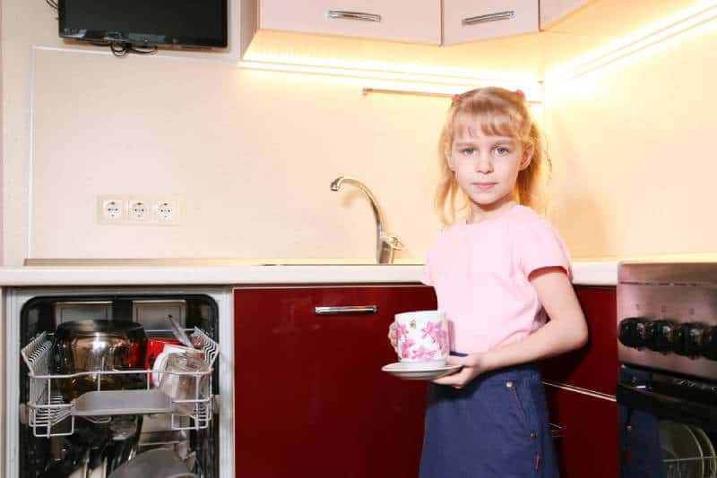 adorable blond girl helping to unload dishwasher