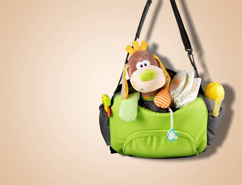 Green diaper bag with a plush toy on brown background