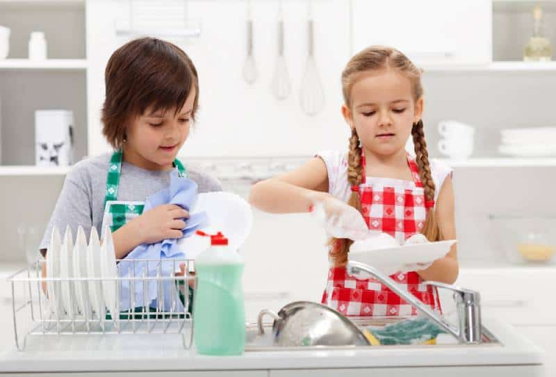 Boy and a girl washing dishes together in the kitchen